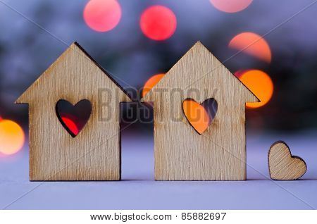 Two Wooden Houses With Hole In The Form Of Heart With Little Heart On Bokeh Background