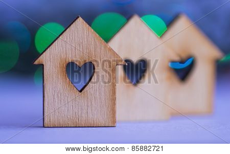 Three Wooden Houses With Hole In Form Of Heart On Colorful Bokeh Background