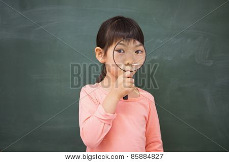 Pupil looking camera with magnifying glass at elementary school