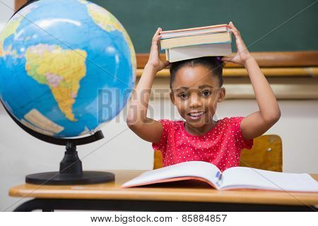 Cute pupil holding books on her head at elementary school