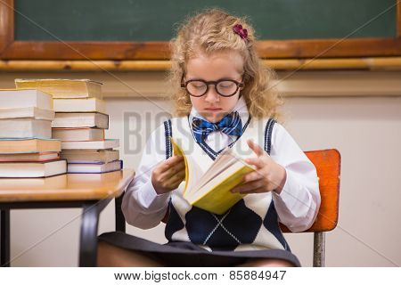Blonde pupil reading a book at elementary school