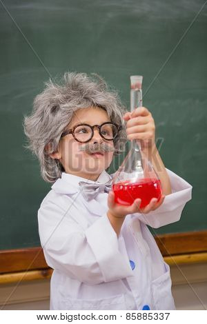 Dressed up pupil looking at red liquid at elementary school