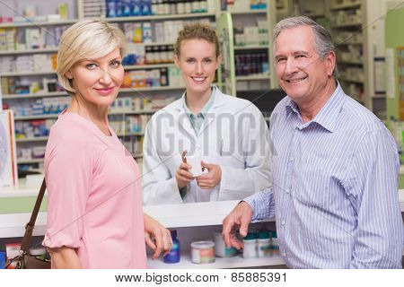 Pharmacist and costumers smiling at camera at pharmacy