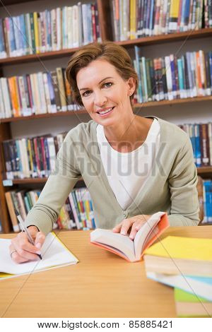 Teacher writing on notepad at library at elementary school
