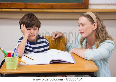 Teacher helping pupil at elementary school