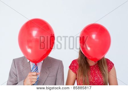 Geeky couple holding balloons in front of their faces on white background
