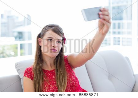 Pretty hipster taking selfie with smartphone on the couch