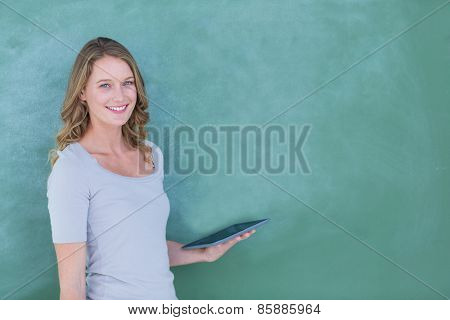 Smiling teacher holding tablet pc in front of blackboard