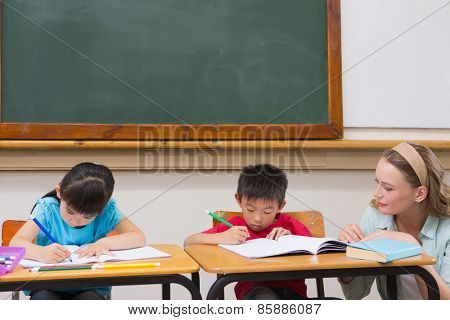 Cute pupils getting help from teacher in classroom at elementary school