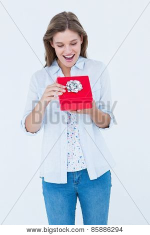 Happy woman opening a present on white background