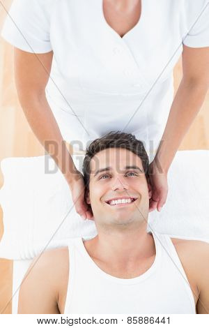Smiling man receiving neck massage in medical office
