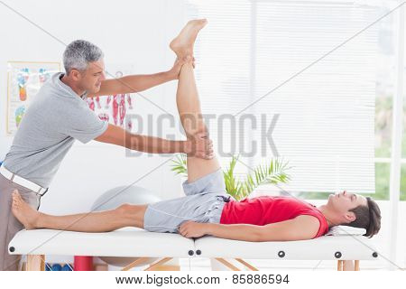 Physiotherapist doing leg stretching to his patient in medical office