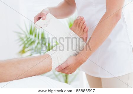 Doctor bandaging her patient ankle in medical office