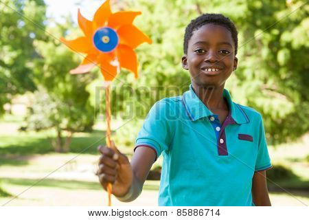 Happy boy in the park with pinwheel on a sunny day