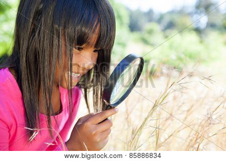 Cute little girl using magnifying glass in park on a sunny day