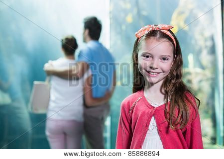 Little girl smiling at camera at the aquarium