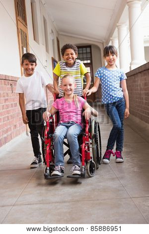 Cute disabled pupil smiling at camera with her friends at the elementary school