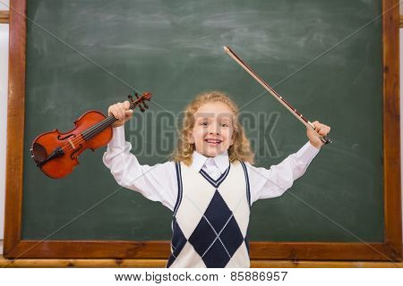 Cute pupil holding violin and violin string at elementary school