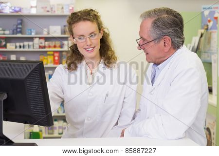Team of pharmacists using computer at pharmacy