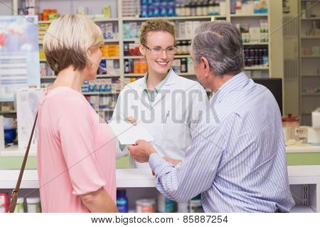 Pharmacist giving prescription to costumer at pharmacy