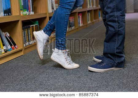 Cute couple embracing each other in the library at the university