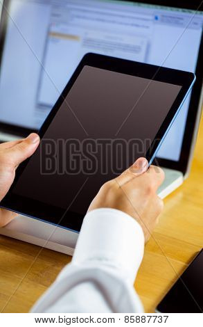 Man using laptop and tablet in close up