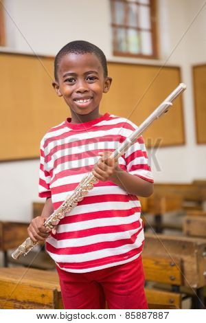 Happy pupil holding flute at elementary school
