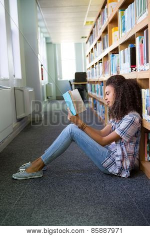 Student sitting on floor in library reading at the university