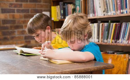 Cute pupils reading in library at elementary school