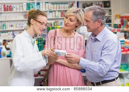 Pharmacist explaining the drug to costumers at pharmacy