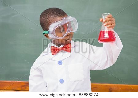 Focus pupil looking at red liquid at elementary school