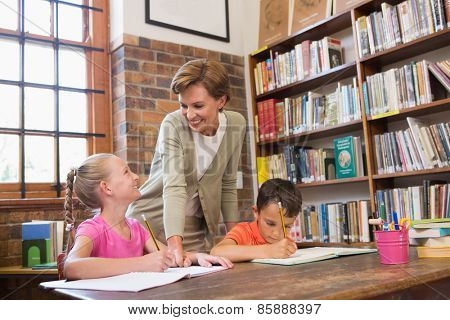 Teacher helping pupils in library at elementary school