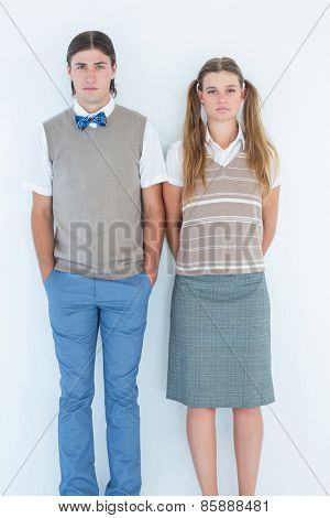 Unsmiling geeky hipsters looking at camera on white background