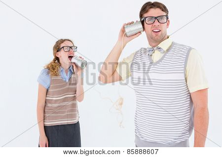 Geeky hipster couple speaking with tin can phone on white background