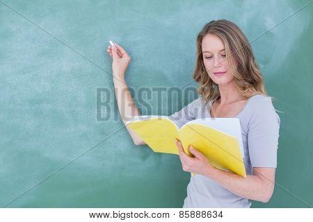 Smiling teacher writing on blackboard in classroom
