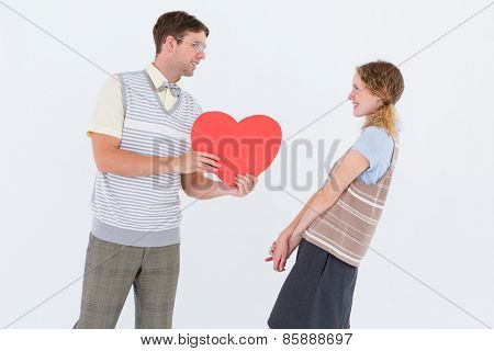 Geeky hipster giving heart card to his girlfriend on white background