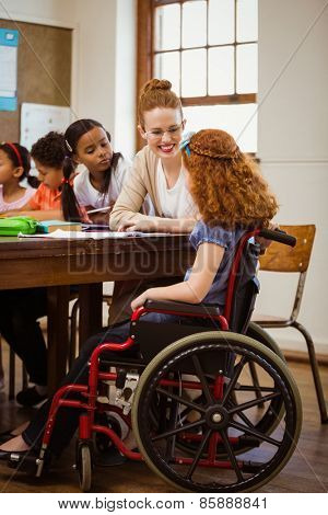 Teacher helping a disabled pupil at the elementary school