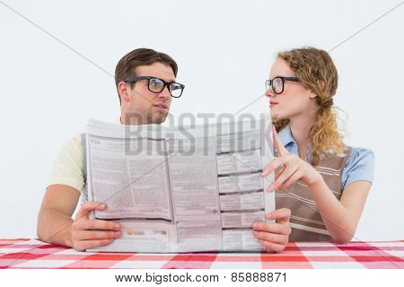 Geeky hipster couple reading newspaper on white background