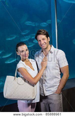 Happy couple beside the fish tank at the aquarium