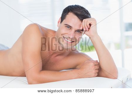 Smiling patient lying on massage table and looking at camera in medical office