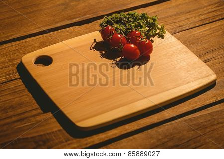 Cherry tomatoes and parsley on chopping board with copy space