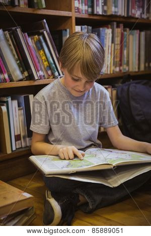 Little boy reading on library floor at the elementary school