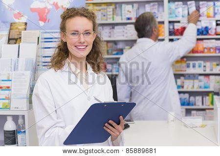 Pharmacist writing on clipboard at the hospital pharmacy