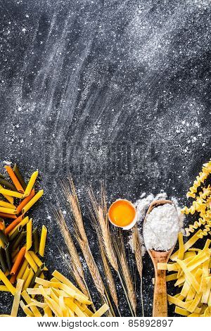 uncooked pasta, flour and other products on a black  textured table
