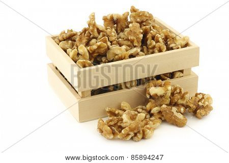 fresh peeled walnuts in a wooden box on a white background