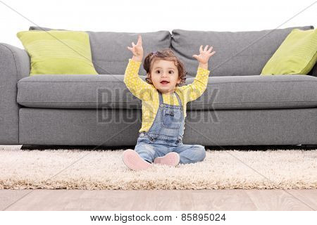 Studio shot of a playful baby girl sitting on the floor next to a modern sofa and gesturing happiness isolated on white background