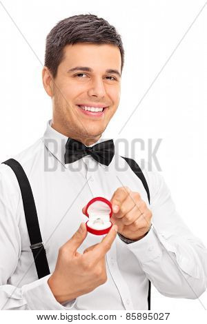 Vertical studio shot of an elegant young man holding an engagement ring, smiling and looking at the camera isolated on white background