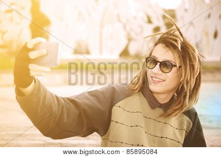 Young Rasta Guy Outdoor Taking Selfie With Smart Phone With A Warm Filter Applied