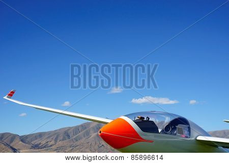Glider under clear blue sky with Benmore Mountain Range in background, New Zealand.