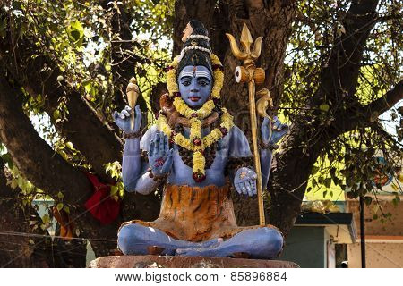 Close-up of Statue of Lord Shiva sitting in meditation under a big peepal tree